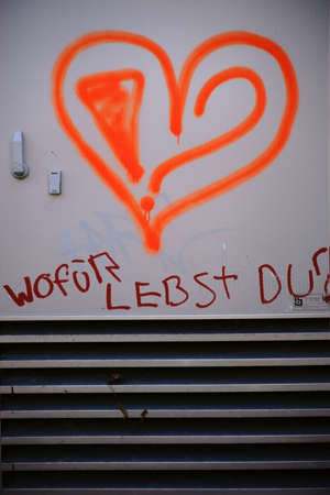 The graffiti of a heart underlined with the slogan or question of meaning: what do you live for.