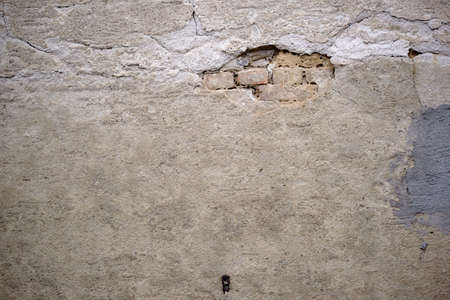 The crumbling plaster layers of an old wall with repair points.