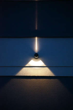 The close-up of a wall spotlight on a smooth concrete wall which generates a light beam and a light cone during the night.