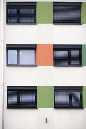 The modern facade of a modern residential building with a metal window with metal blinds.                      Stockfoto
