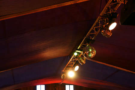 A lighting system with disco lights, light emitters and a disco ball under the roof of a building.