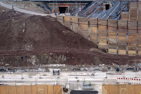 The side view of a excavated and fortified excavation of a construction site with worn and heaped up sand piles of earth.