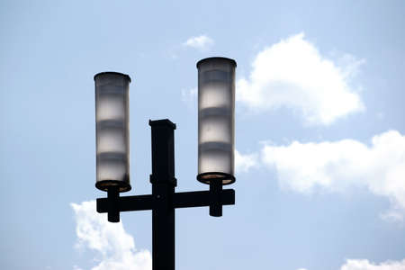 The two lampshades of a modern street lamp in front of a blue sky with clouds.