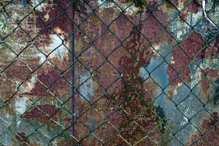 A heavily rusted iron door with rust bubbles damage behind a chain link fence.