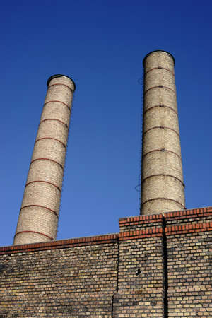 The disused chimneys of a factory with brick industrial buildings.