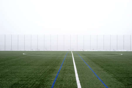 The green lawn of a football field in the fog.