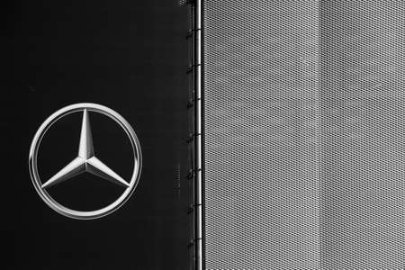 Mainz, Germany - April 06, 2018: The symbol and the shiny star of Mercedes Benz on the modern facade of a dealership on April 06, 2018 in Mainz.