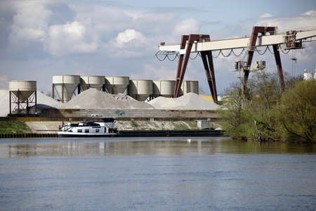 A transport ship drives into an inland port of the river Main in Ruesselsheim with storage and accumulated building materials.
