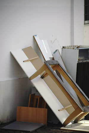 Bulky waste such as furniture and wood waste and a refrigerator are leaning against a wall.                        스톡 콘텐츠
