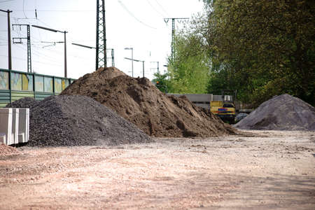 The excavated soil with sand piles of a construction site at the railway tracks.                               Stock Photo