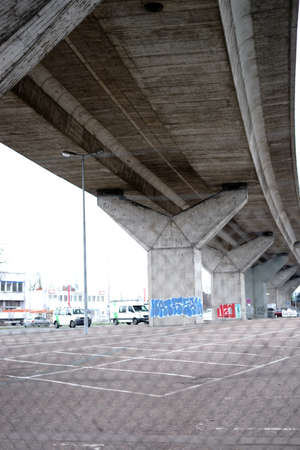 A fenced parking lot in the city under a bridge with lanes a main road.