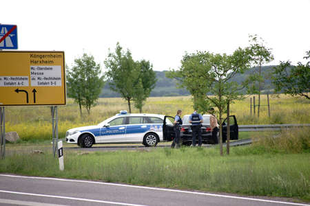 Mainz, Germany - June 17, 2018: A police ambulance with two police officers carry out a car driver on the roadside on June 17, 2018 in Mainz.