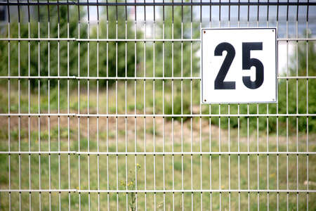 The detail of a lattice fence with the numbering of a fenced plot. Reklamní fotografie