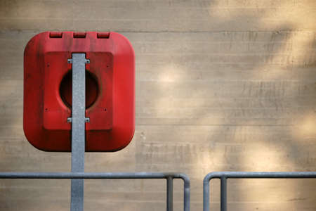 Emergency equipment with a lifebuoy on the railing and the outer wall of a weir. Stock Photo