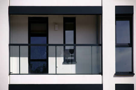 The glass railing of a new and modern balcony of an apartment and and multi-family house.