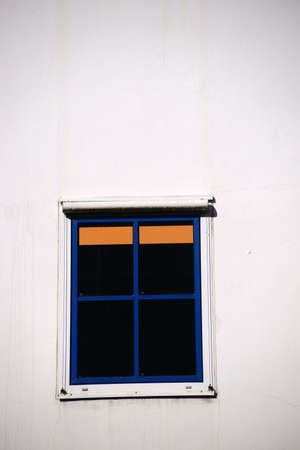 An abstract window with blue window frame and orange venetian blind in the sunlight.