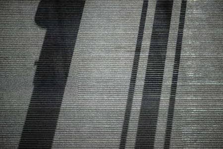 The closeup and top view of a corridor with gray carpeting and abstract shadows.