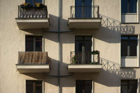 The railings of small nostalgic balconies of an apartment building cast shadows.