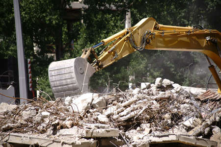 An excavator stands at a construction site of an industrial building and removes the debris.