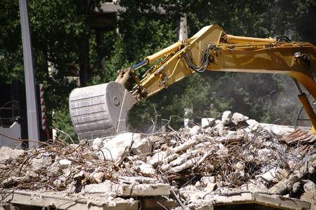 Une excavatrice se trouve sur un chantier de construction d'un bâtiment industriel et enlève les débris.