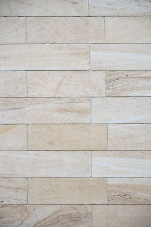 A light beige cladding made of marbled sandstone with pores.