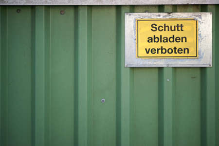 A metal container wall with a warning sign with inscription: Dump debris prohibited.