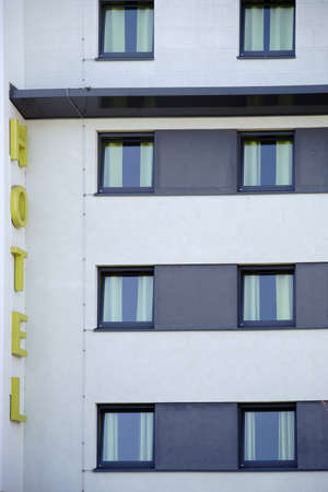A modern hotel facade with sign and window fronts.