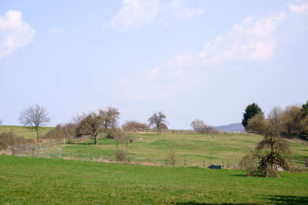 A hilly landscape with meadows and a pasture fence. 写真素材