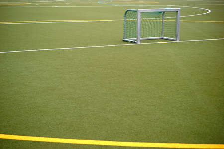 The close-up of an artificial turf field for football matches and field hockey with colored lines and color markings.
