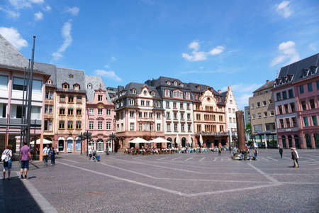 Mainz, Germany - May 27, 2019: People are sitting outside of cafes on the market square with the Heunensaeule on May 27, 2019 in Mainz.