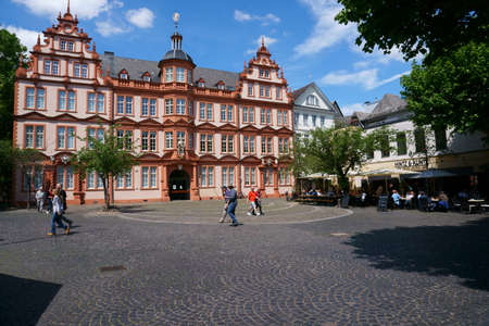 Mainz, Germany - May 27, 2019: Pedestrians and passers-by as well as restaurant visitors of the Hintz and Kuntz in front of the Gutenberg Museum on May 27, 2015 in Mainz.