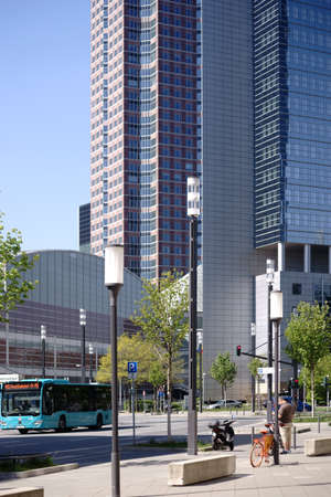 Frankfurt, Germany - April 18, 2019: Bus traffic and infrastructure in front of the Festhalle Messe Frankfurt and the Kastor skyscraper on April 18, 2019 in Frankfurt.