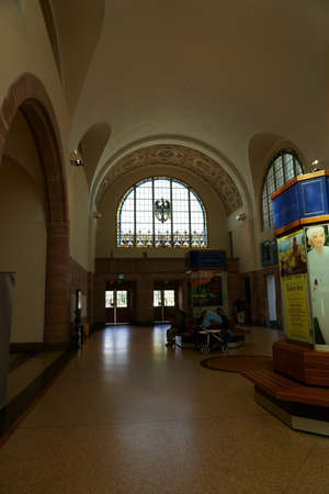 Bad Homburg, Germany - June 09, 2019: Travelers sit at advertising pillars in the interior of the main train station on June 09, 2019 in Bad Homburg.