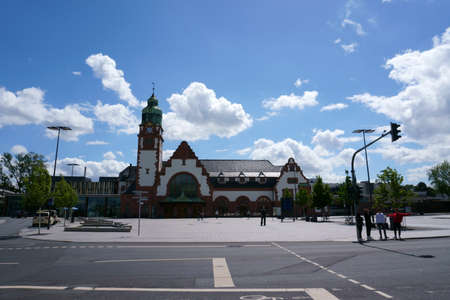 Bad Homburg, Germany - June 09, 2019: Tourists and travelers on the forecourt of the historic main train station on June 09, 2019 in Bad Homburg. Sajtókép