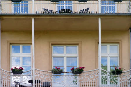The facade of a villa with a terrace or a Venetian-style balcony with balcony flowers.