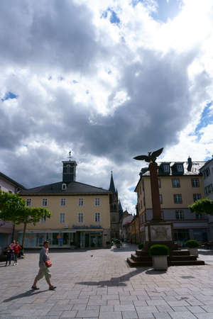 Bad Homburg, Germany - June 09, 2019: Passers-by cross the Waisenhausplatz with the memorial and adjoining shop on June 9, 2019 in Bad Homburg.