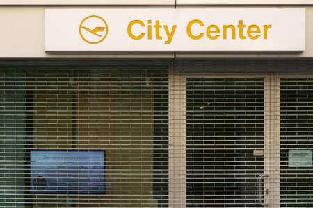 Frankfurt, Duitsland - 06 juli 2019: Het logo van het reisbureau Lufthansa City Centre boven de versperde etalage van een gesloten winkel op 06 juli 2019 in Frankfurt.