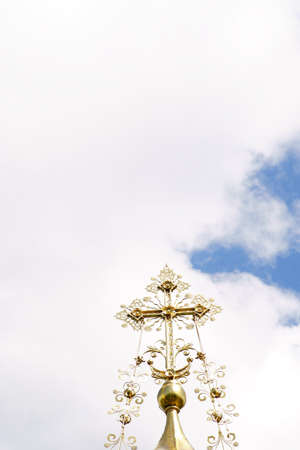 The ornate golden cross of a Russian chapel in front of a blue sky.