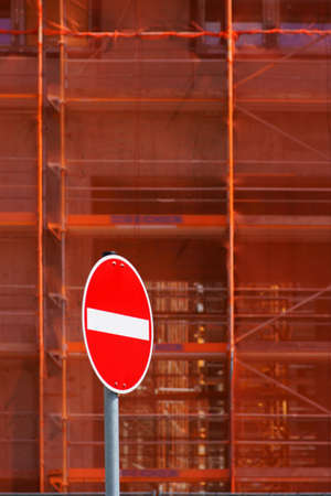 The close-up of a scaffolding with buttresses and safety nets in front of which stands a red one-way street sign. Reklamní fotografie