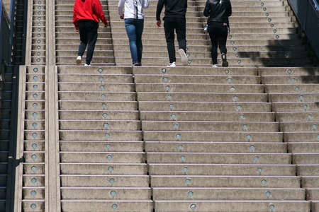 The legs and feet of a group of young people going up an outdoor staircase.