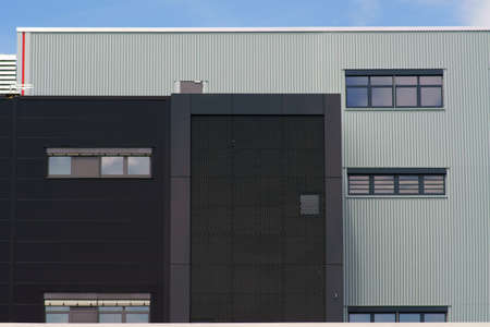 A modern industrial building with various sheet metal facades and grilles.