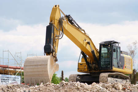 A non-working excavator stands on the rubble heap of a construction site.