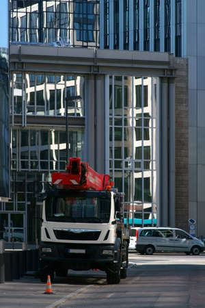 A truck with a lift stands in front of modern office buildings in the city center of Frankfurt. Reklamní fotografie