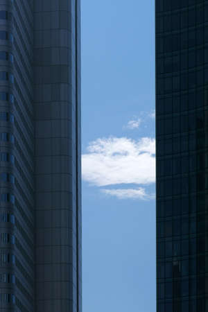 A cloud and the blue sky between the corners and side edges of two modern skyscrapers. Reklamní fotografie