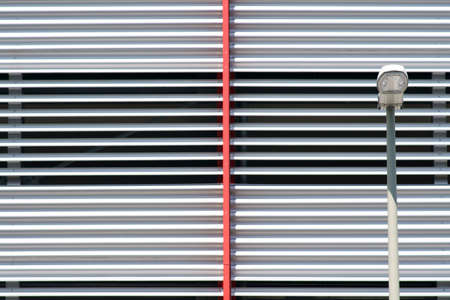 A street lamp in front of the modern metal paneling of a parking garage. Reklamní fotografie