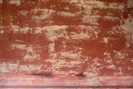 The close-up of peeling clay colored wall paint on a wall.