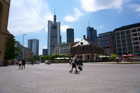 Frankfurt, Germany - July 06, 2019: Pedestrians and visitors strolling through town on the square in front of the Hauptwache with skyscrapers of the financial district in the background on July 06, 2019 in Frankfurt.