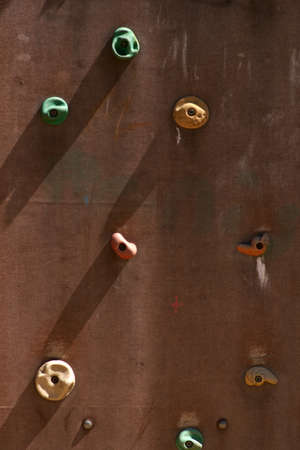 The close-up of a climbing wall with rubber rungs.