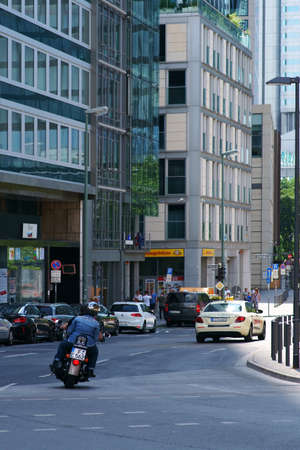 Frankfurt, Germany - July 06, 2019: Road traffic with a motorcycle at Thurn and Taxis Square at the city center on July 06, 2019 in Frankfurt.