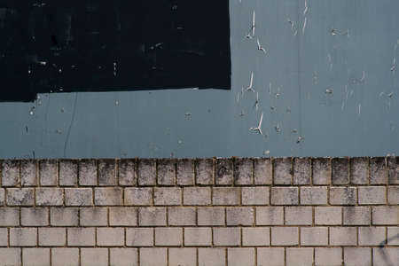 The close-up of a gray billboard with torn pieces of paper over a bright wall edge. Reklamní fotografie